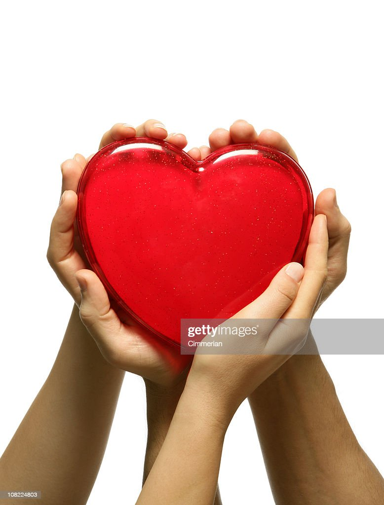 Man and Woman's Hands Holding Plastic Red Heart : Stock Photo