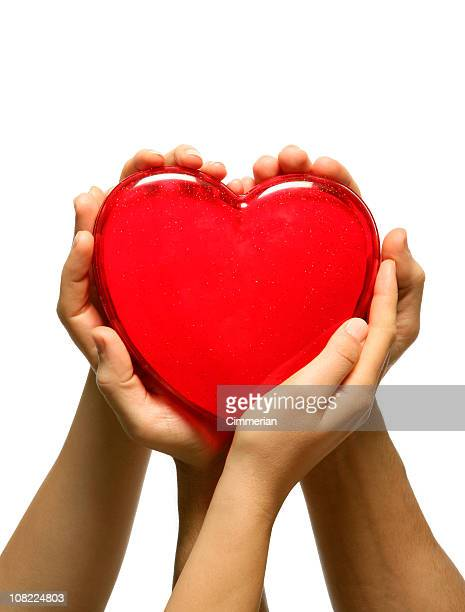Man and Woman's Hands Holding Plastic Red Heart