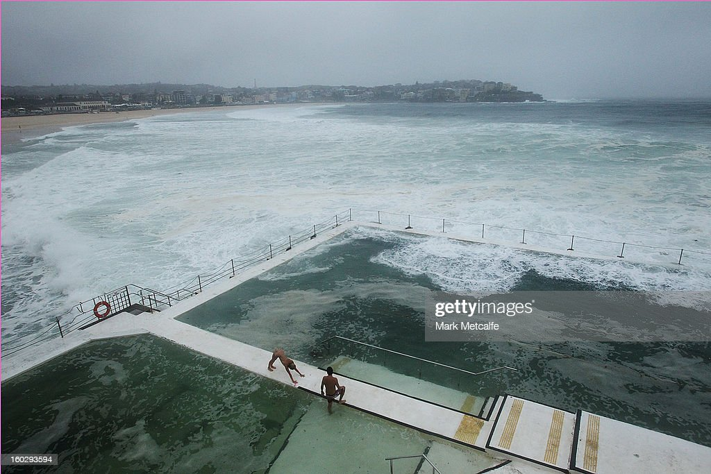 A man and women brave the rough and dirty conditions at Bondi Icebergs pool after winds and rain battered Sydney last night on January 29, 2013 in Sydney, Australia. Parts of Sydney are experienced record rainfall after ex-cyclone Oswald swept through the city last night.