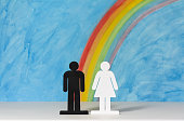 Man and women icons with a rainbow and blue sky to illustrate the concept of gender equality; copy space.