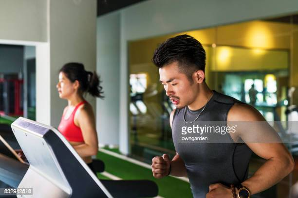 Man and women jogging on treadmills at gym