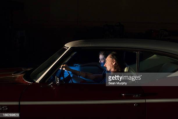 A man and women sitting in a vintage car at night