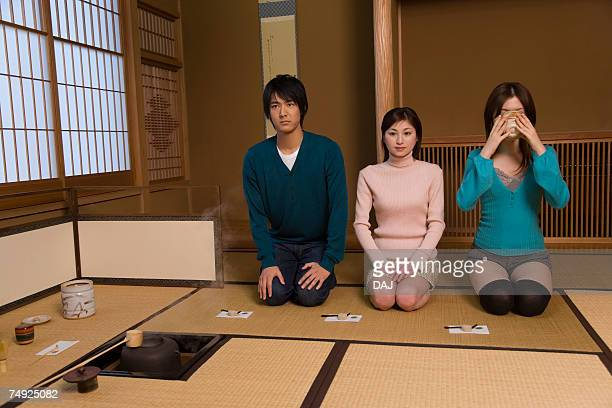 Man and women sitting in tea room, one drinking Japanese tea, front view, Japan