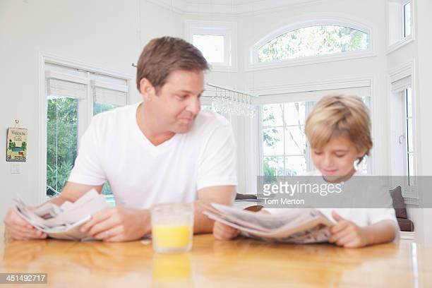 Homme et jeune garçon de rire en lisant un journal et cuisine