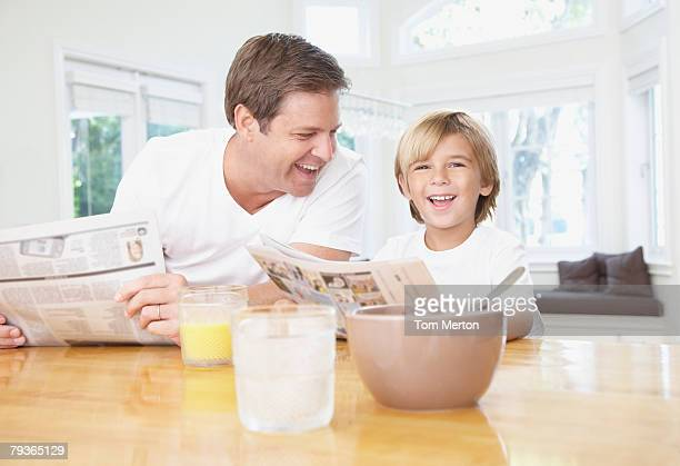 Man and young boy in kitchen reading newspaper and laughing
