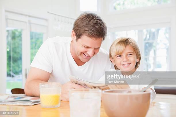 Uomo e giovane ragazzo in cucina lettura giornale