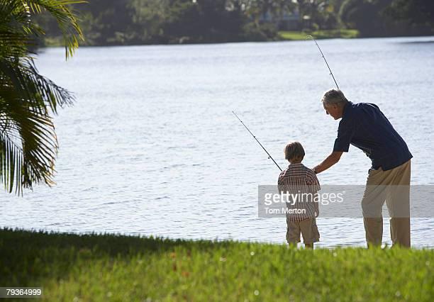 Mann und Junge Jungen draußen im park, Fischen im See