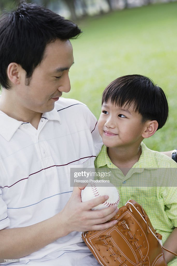 Man and young boy outdoors at park with baseball and glove : Stock Photo