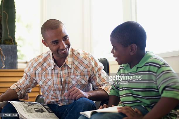 Mann und Junge sitzen mit Zeitung und buchen