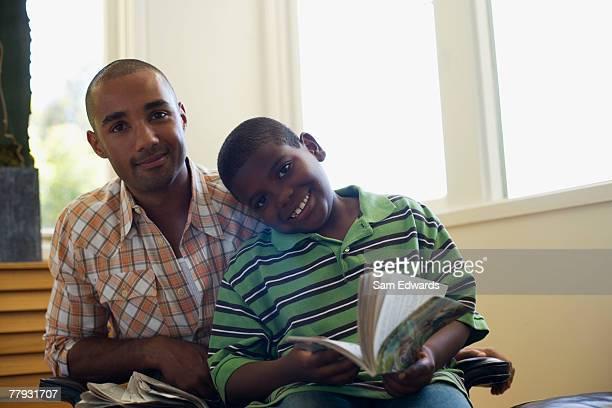 Mann und Junge Jungen mit Zeitung und Buch im Wohnzimmer
