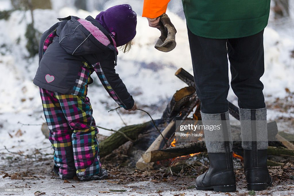 A man and young child warm themselves next to a camp fire after choosing and cutting down their Christmas tree in a forest on on December 8, 2012 in Fischbach, Germany. Forestry officials in the state of Saxony officially opened the 2012 Christmas tree season for people who want to retrieve their tree from designated forests rather than just buying it readily cut.