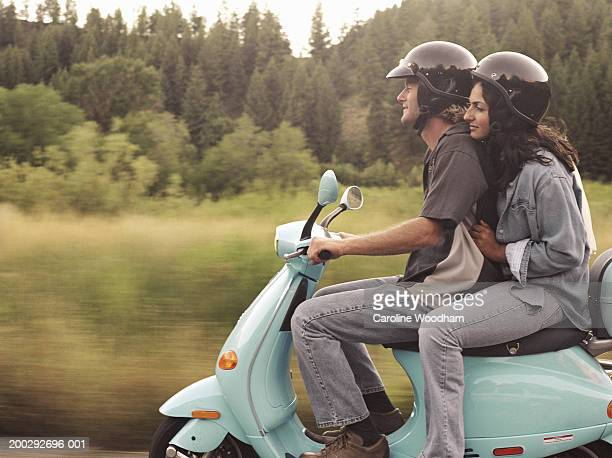 Man and young woman riding on motor scooter, side view