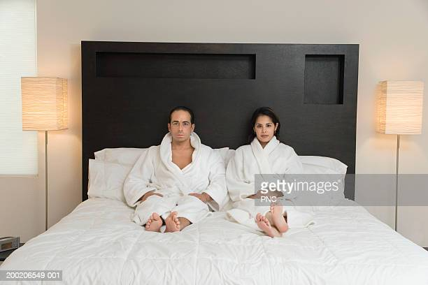 Man and young woman sitting on bed, wearing bathrobes, portrait