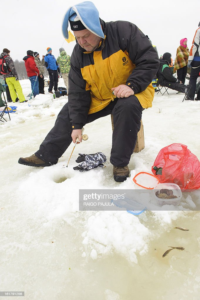 STORY - A man angles a fish sitting on the frozen lake Viljandi, in Viljandi, Estonia during a ice fishing event on February 16, 2013. More than 8,000 participants from different countries arrived for the fishing event.