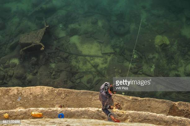 A man angles with a handheld fishing line from a wall on the seafront of the city of Piraeus near Athens The sea floor is littered with rubble and...