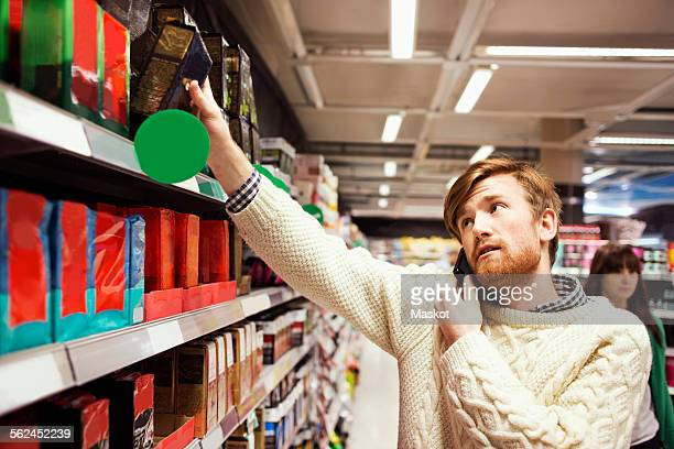Man answering mobile phone while shopping at supermarket