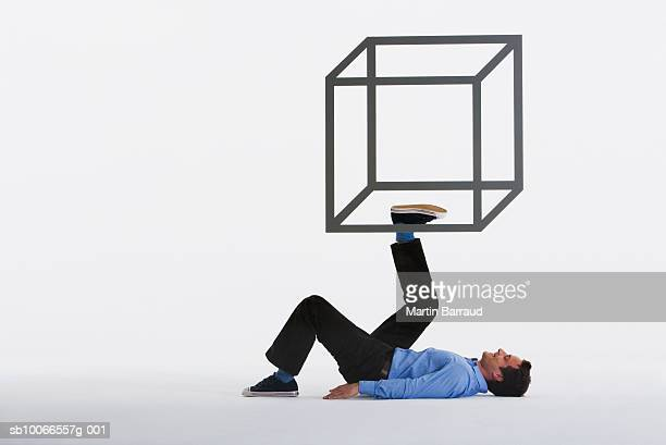 Man appearing to hold up outline of geometric box with foot