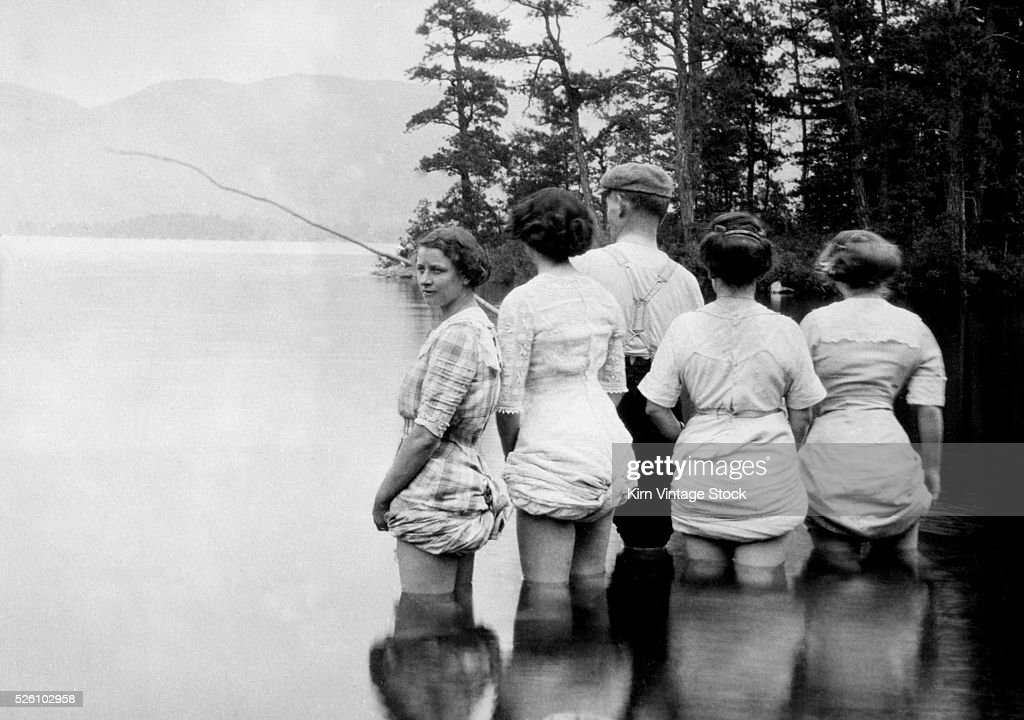 A man appears to be giving fishing lessons to a group of women with their dresses hiked up, ca. 1915