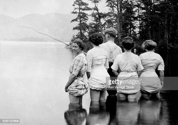 A man appears to be giving fishing lessons to a group of women with their dresses hiked up ca 1915