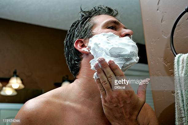 A man applying a shaving cream to his face