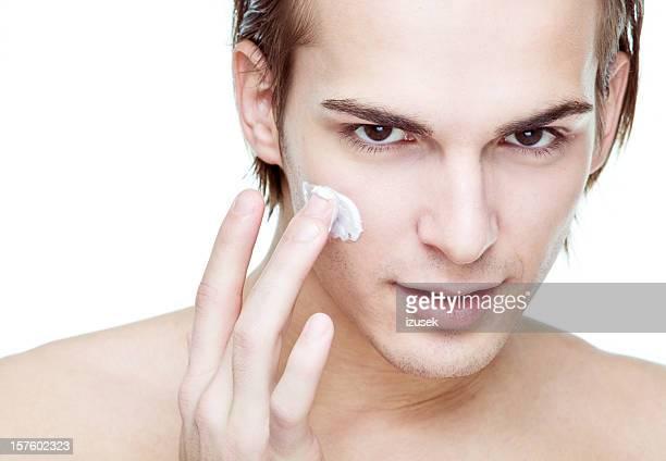 Mann, die Anwendung kosmetische Creme auf Gesicht