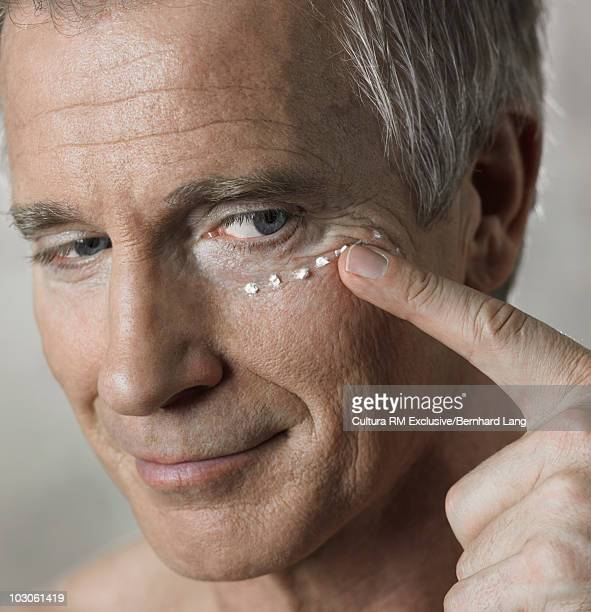 Man (53y) applying eye creme, close up