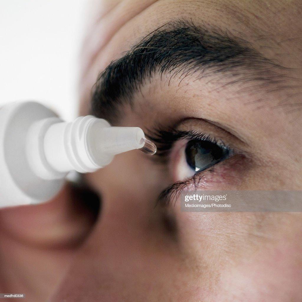 Man applying eye drops into eye, extreme close-up : Stock Photo