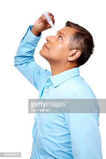 Man applying eye drops to his eyes.