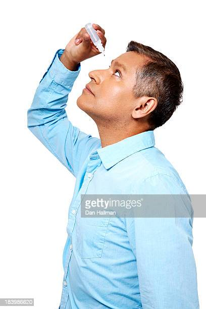 Man applying eye drops to his eyes.