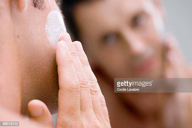 Man applying face cream in front of mirror