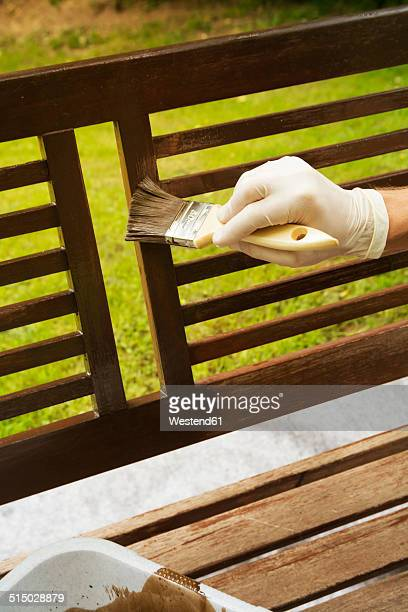 Man applying glaze on wooden bench, partial view