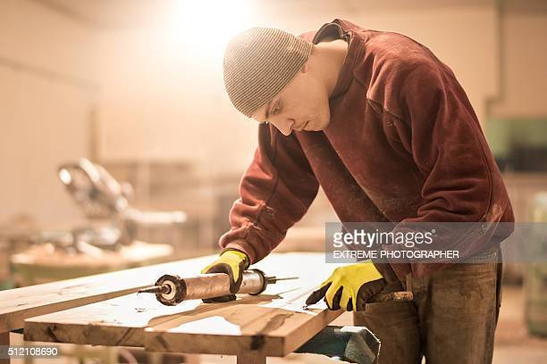 Man applying glue on wooden plank