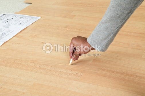 Man Applying Laminate Repair Compound To Scratch On Wood Laminate