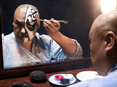 Man applying makeup for Chinese Opera