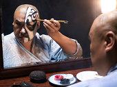 Man applying makeup for Chinese Opera