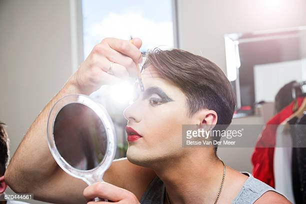 man applying makeup, holding mirror.