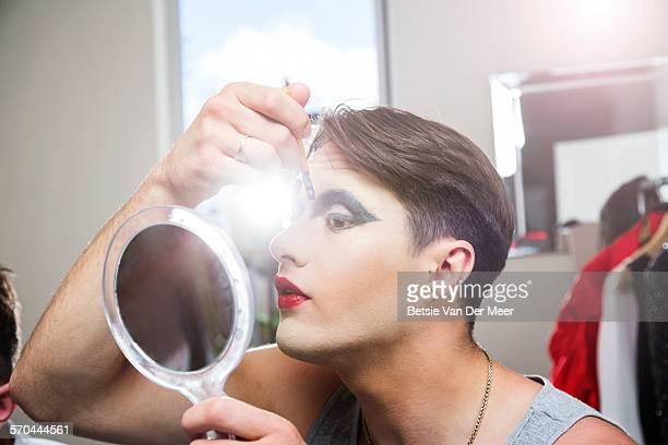 man applying makeup, holding mirror.
