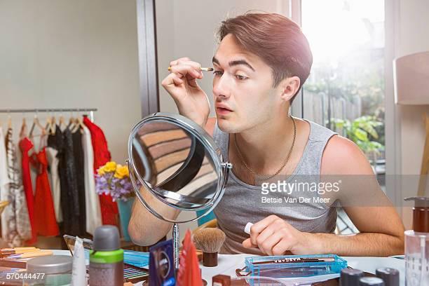 Man applying makeup in domestic setting.