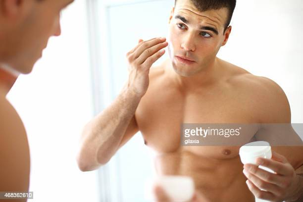 Man applying moisturizer.