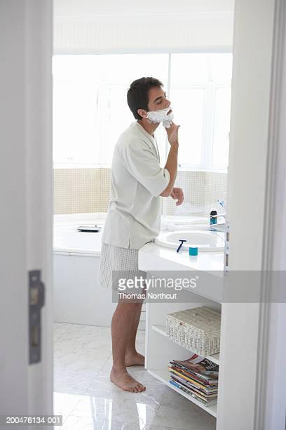 Man applying shaving cream to face in bathroom mirror, side view