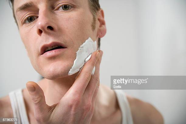 Man applying shaving cream to face