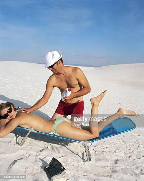 Man applying suntan lotion on woman's back, close-up