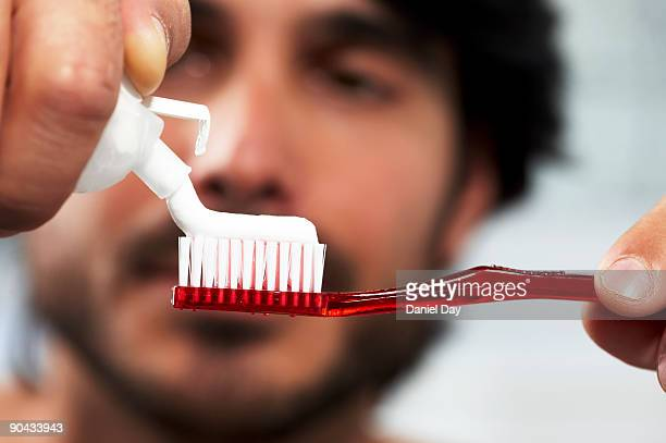 Man applying toothpaste to brush