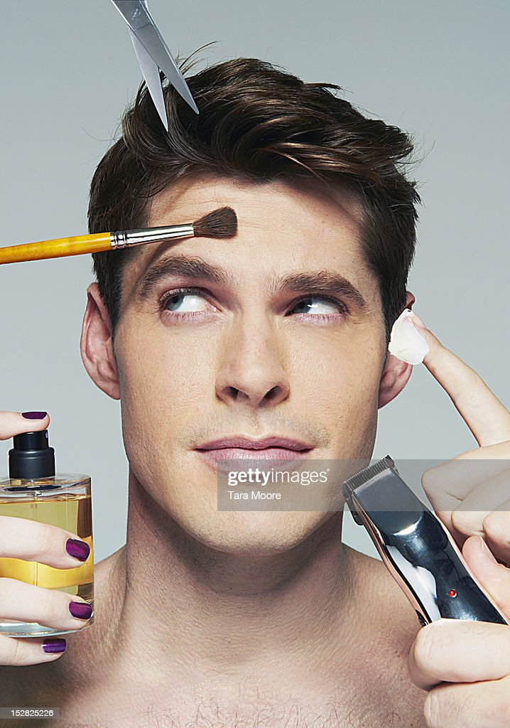 man applying various beauty products to face : Stock Photo