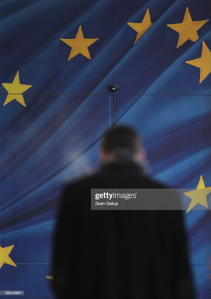 A man approaches the glass door decorated as the flag of the European Union at an entrance to the Berlaymont building of the European Commission on November 17, 2011 in Brussels, Belgium. Eurozone member countries are continuing to struggle with a debt crisis afflicting a widening circle of nations as the rest of the world fears economic repurcussions.
