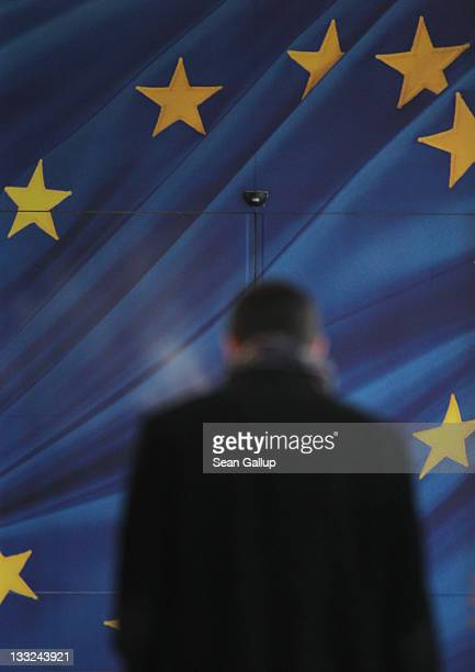A man approaches the glass door decorated as the flag of the European Union at an entrance to the Berlaymont building of the European Commission on...