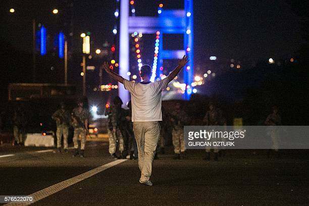 A man approaches Turkish military with his hands up at the entrance to the Bosphorus bridge in Istanbul on July 16 2016 Turkish security forces on...