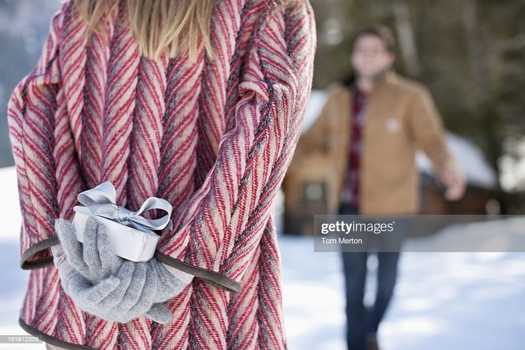 Man approaching woman with Christmas gift behind back : Stock Photo