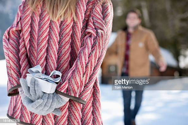 Man approaching woman with Christmas gift behind back