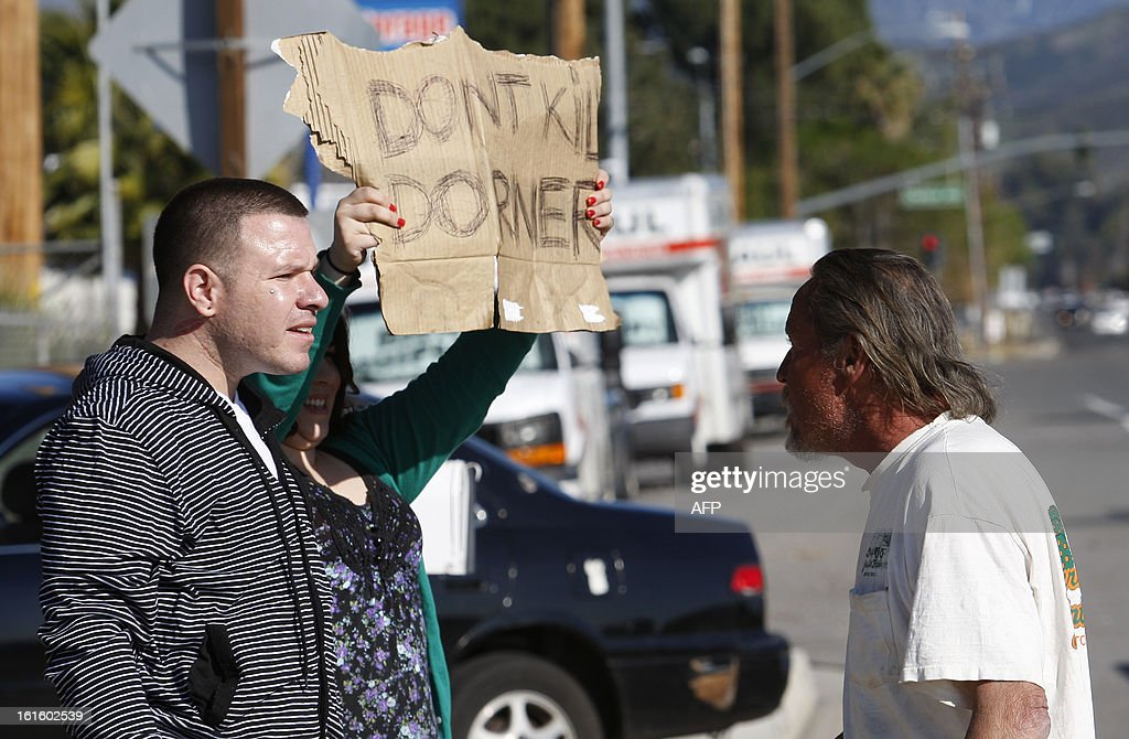 A man argues with Frank Cardiel (L) and Shantel Cardiel who hold signs in support of fugitive triple murder suspect Christopher Dorner along the road in San Bernardino, California n February 12, 2013. Fugitive former US cop Christopher Dorner exchanged gunfire with police near a Californian ski resort where his burnt-out truck was found, reports said. The 33-year-old was involved in the shooting after he tried to burglarize a home near Big Bear, two hours east of Los Angeles, the Los Angeles Times reported, citing a law enforcement source.   AFP PHOTO / David McNew